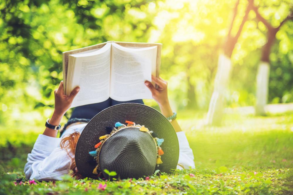 Frau liegt auf der Wiese und liest ein Buch