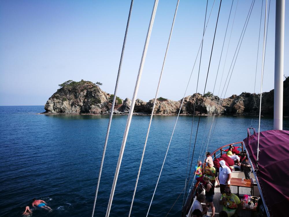 Menschen erfrischen sich neben dem Partyboot im Meer.