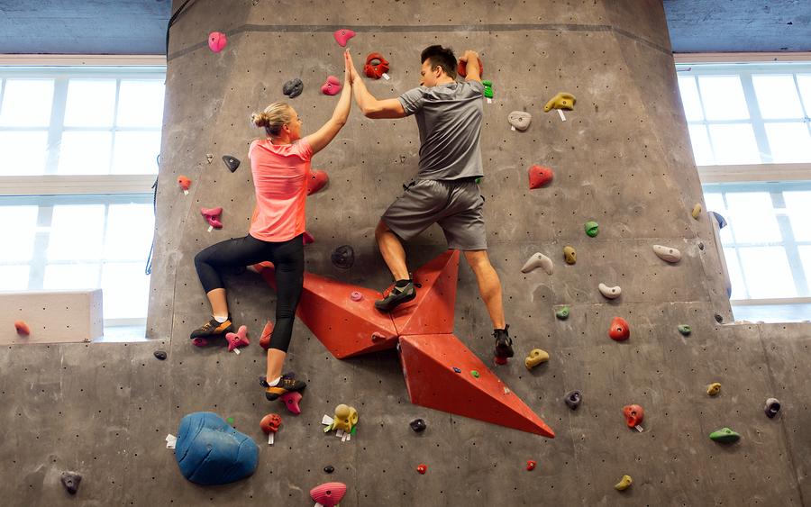 Frau und Mann klettern oder bouldern und geben sich ein High Five.