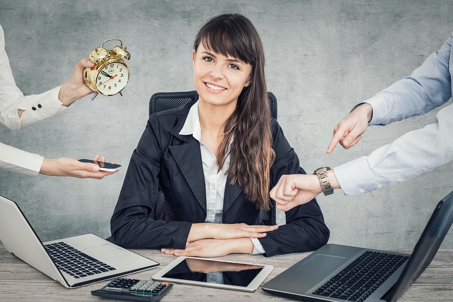 Frau im Büro lächelt, obwohl sie unter Zeitdruck steht.