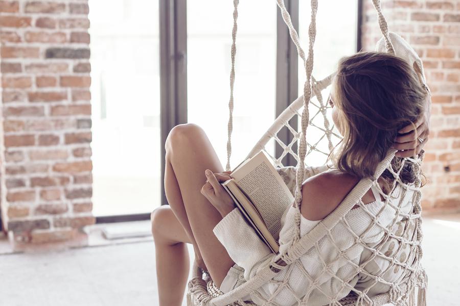 Frau entspannt beim Lesen in Hängesessel.
