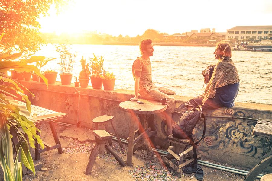 Mann und Frau sitzen auf einer Mauser an einem Fluss im Abendlicht.