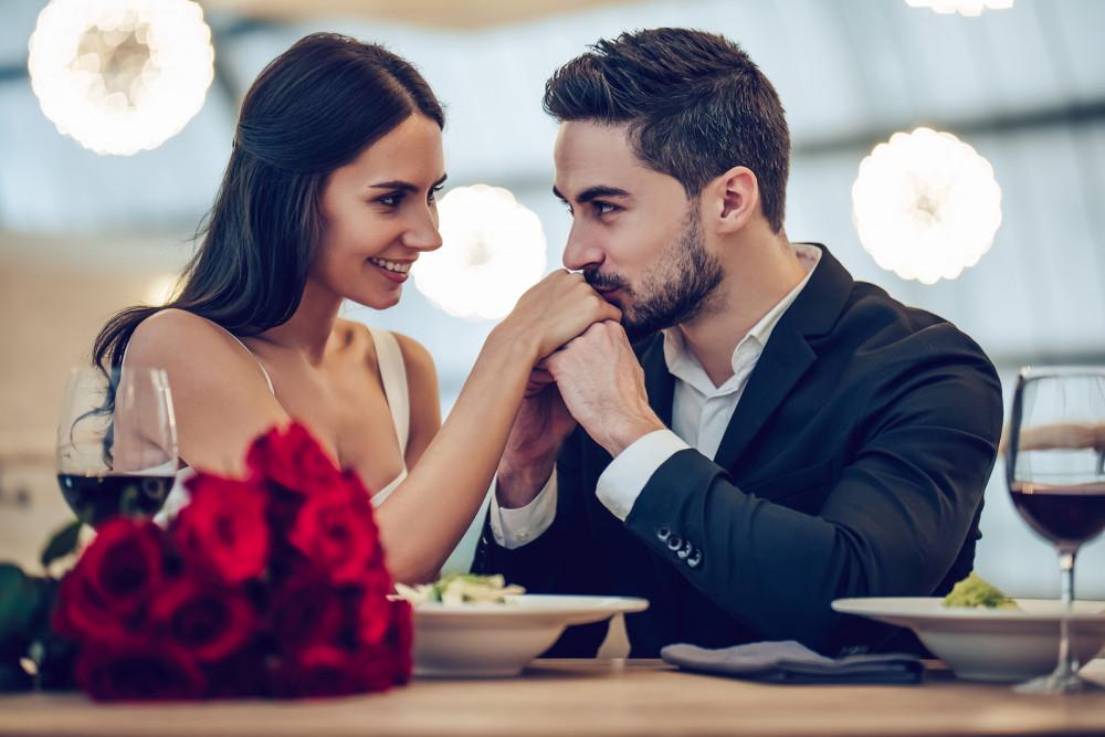 Glückliches Paar beim Date im Restaurant mit Rotwein und Rosen.
