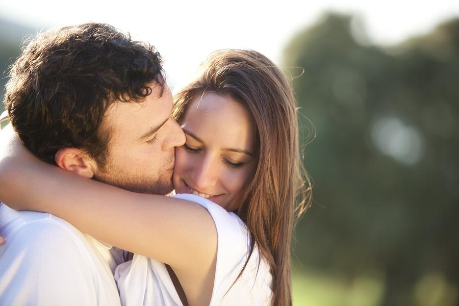 Verliebtes Paar umarmt sich, er küsst sie auf die Wange.