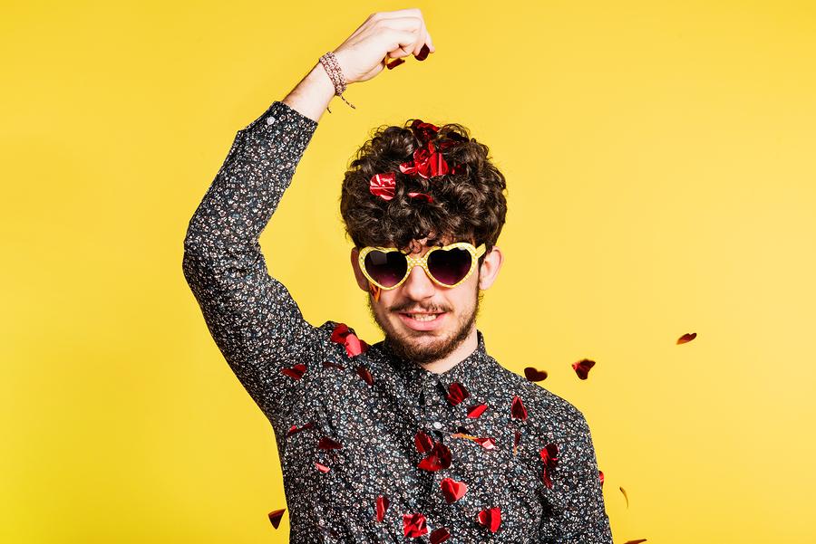Junger Mann mit Herzsonnenbrille streut sich Herzglitzer über den Kopf.