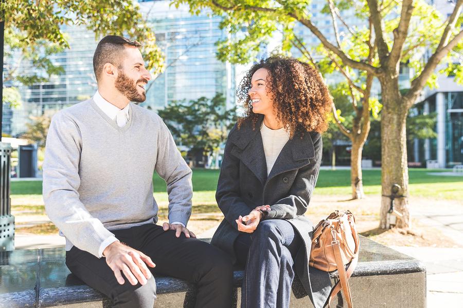 Frau und Mann unterhalten sich auf Parkbank und lachen.