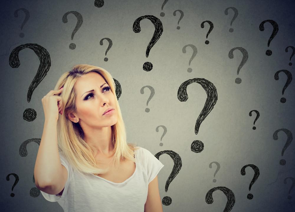 Blonde Frau umgeben von Fragezeichen.