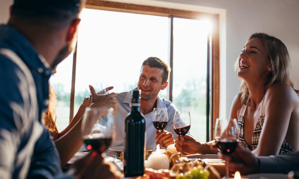 Freunde sitzen bei einem gemeinsamen Glas Wein um einen Esstisch und prosten sich zu.