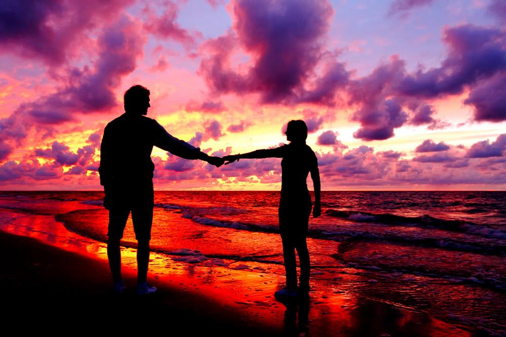 Verliebtes Paar hält Händchen vor Sonnenuntergang am Strand.