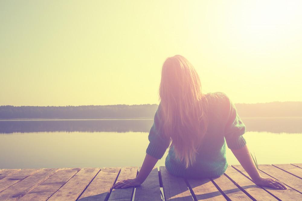 Junge, blonde Frau sitzt auf Holzsteg am See.