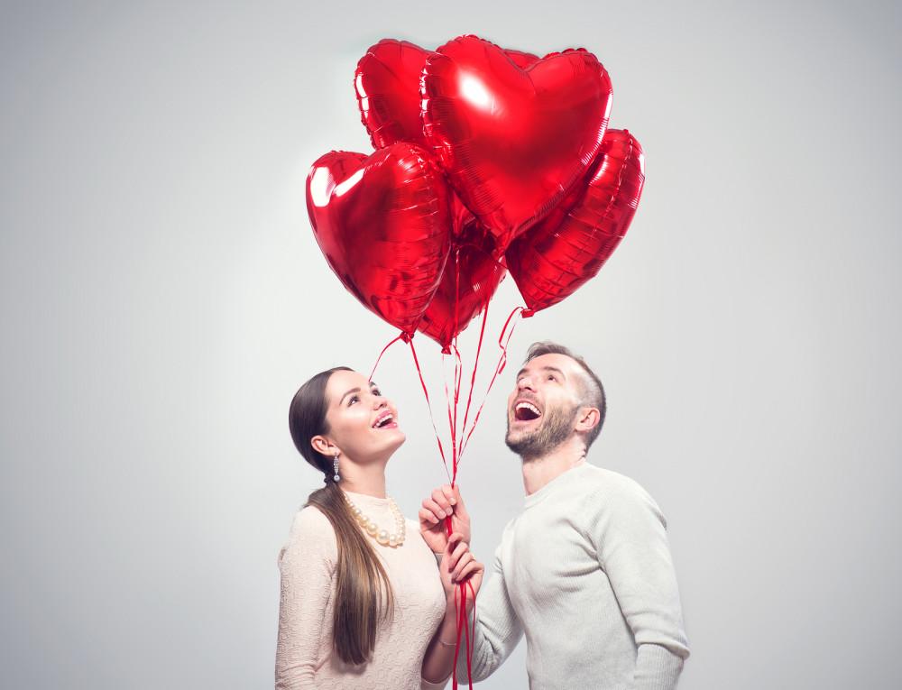 Frau und Mann schauen zu roten Herzluftballons hoch, die sie festhalten.