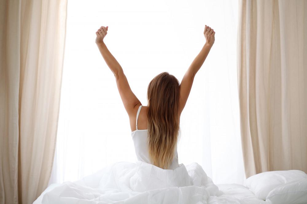 Frau streckt am Morgen sich auf einem Bett sitzend.