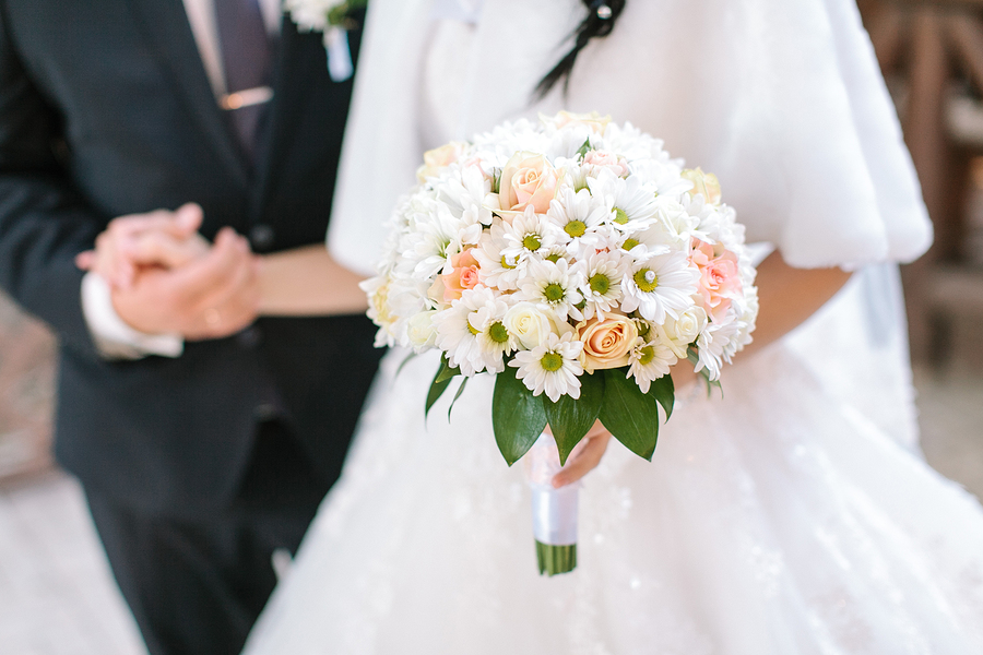 Schöner Brautstrauß im Vordergrund, verschwommen das Brautpaar im Hintergrund.