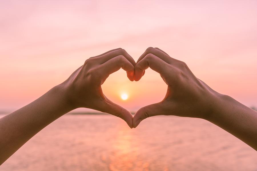 Zwei Hände formen ein Herz um die untergehende Sonne.