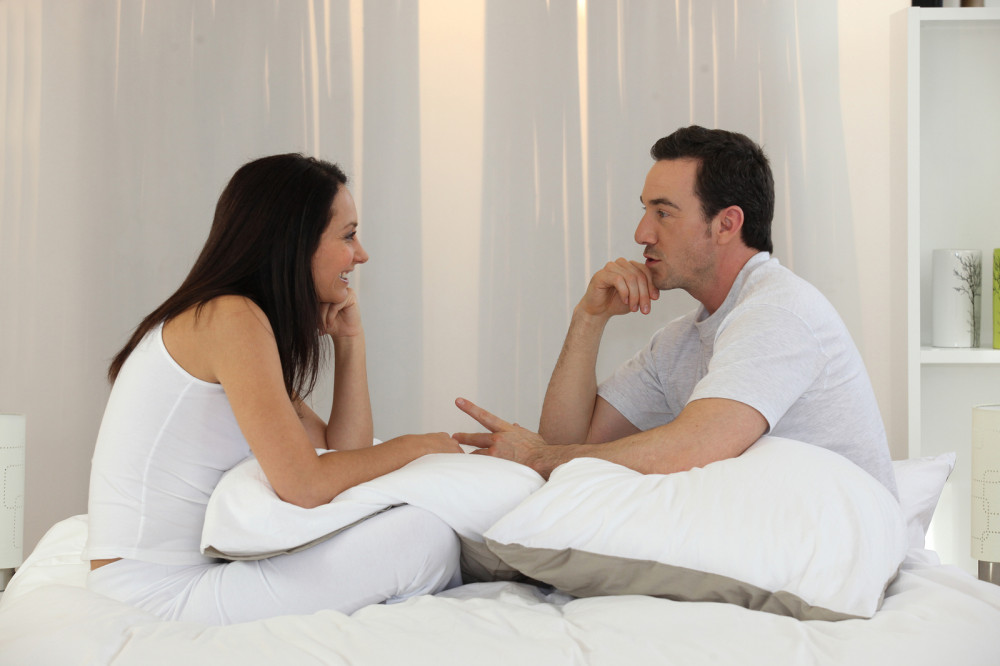 Pärchen sitzt auf dem Bett und redet über Wünsche und Vorstellungen.
