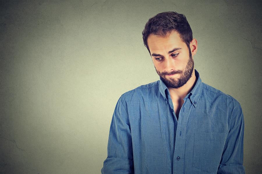 Schüchterner Mann steht mit verkniffenem Gesicht vor grauer Wand