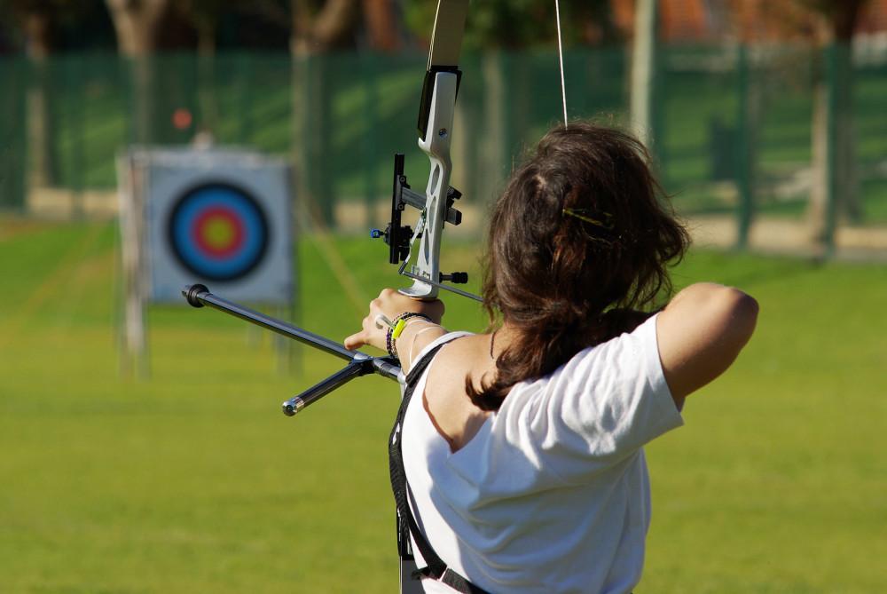 Sütze Frau schießt mit Pfeil und Bogen auf eine Zeilscheibe.