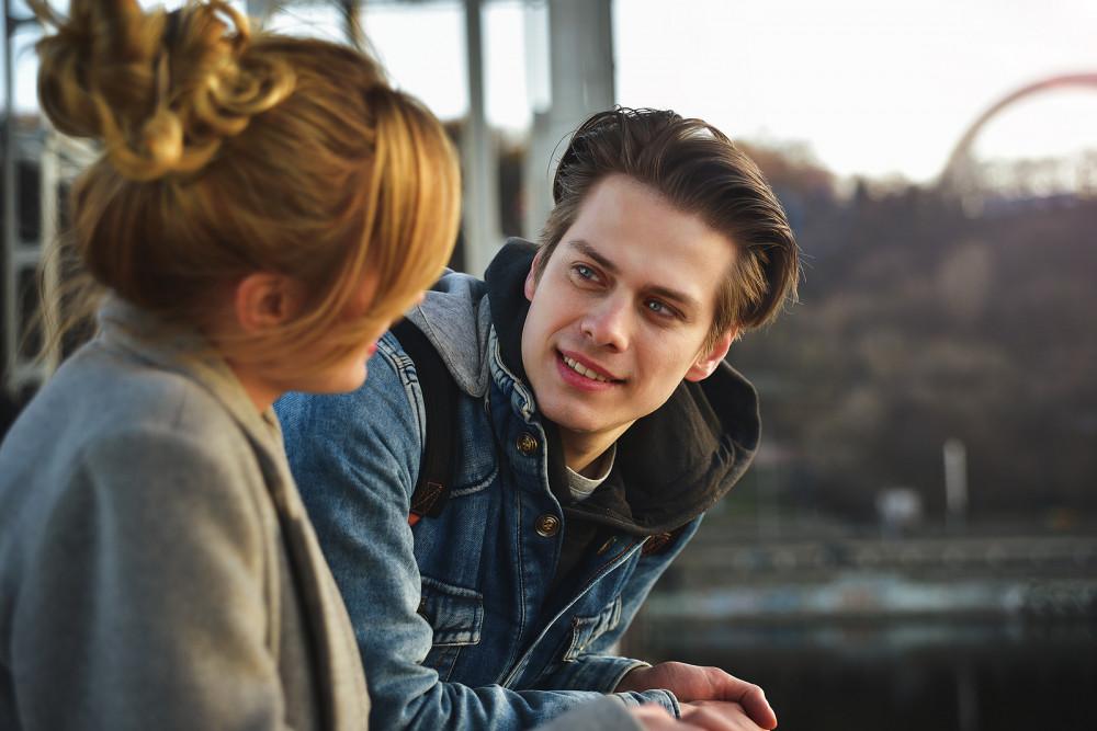 Junge Frau und junger Mann bei intensivem Gespräch auf einer Aussichtsplattform.