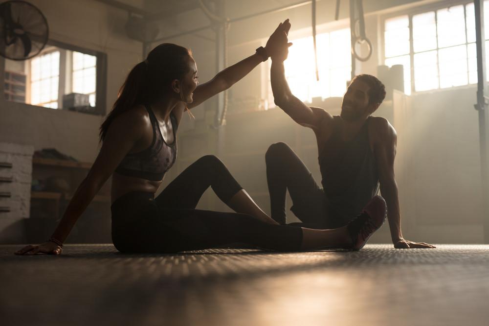 Pärchen gibt sich nach dem zusammen absolvierten Sport ein High Five.