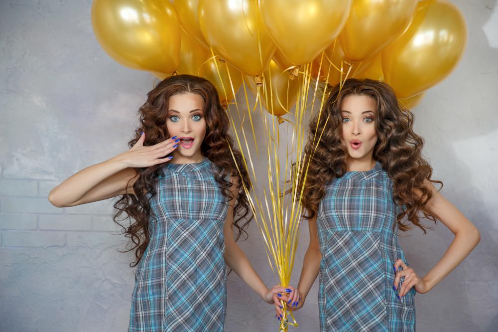 Junge brünette Zwillingsfrauen halten zusammen einige goldene Luftballons an Bändern und schauen überrascht.