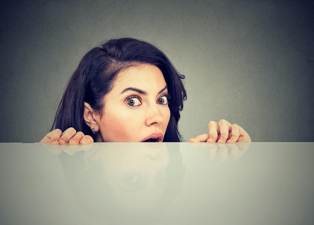 Frau versteckt sich staunend hinter einer Tischplatte.