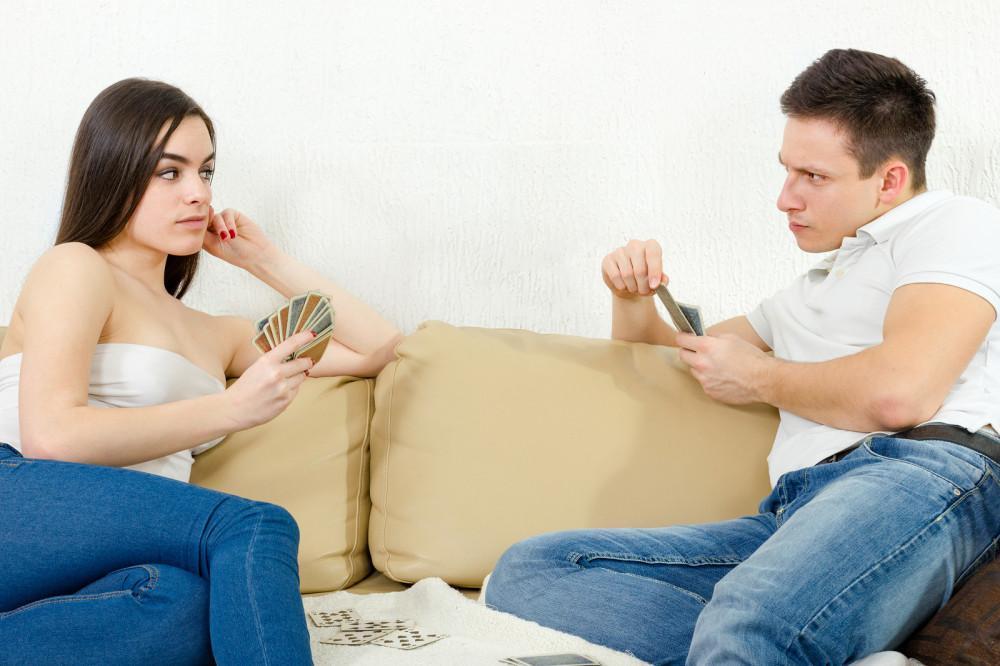 Paar spielt Karten und schaut sich skeptisch an.