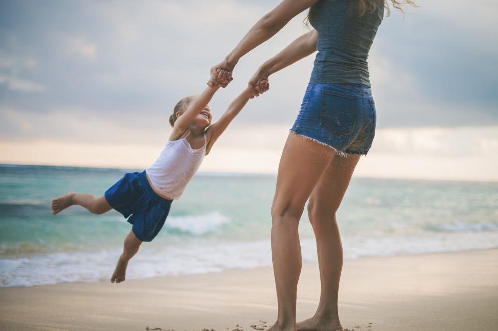 Mutter schwingt Kind am Strand im Kreis.