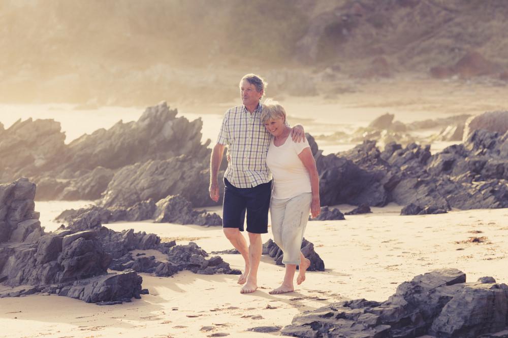 Paar genießt Ruhestand bei einem Spaziergang am Strand.
