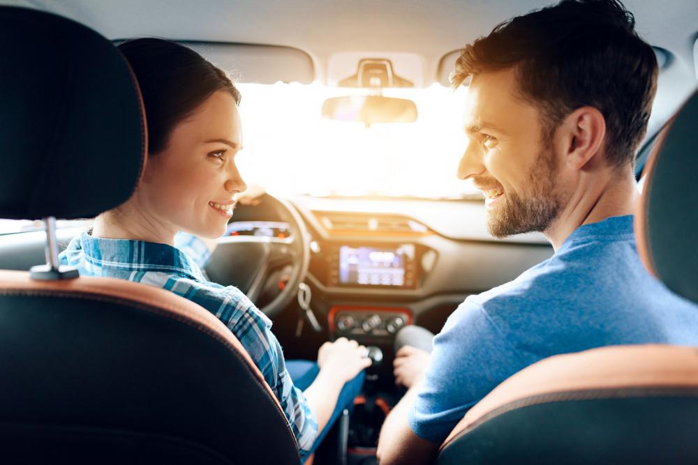 Paar schaut sich verliebt im Auto an.