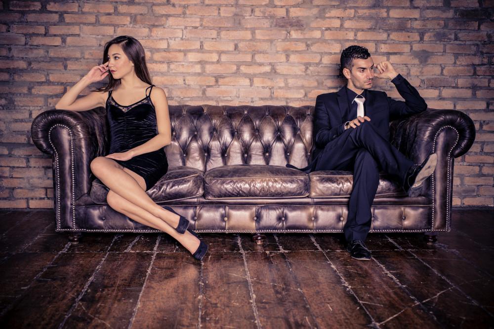Frau und Mann sitzen an den jeweils anderen Enden des Sofas.