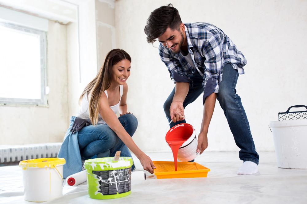 Junges Paar beim gemeinsamen Renovieren und Streichen der Wohnung.