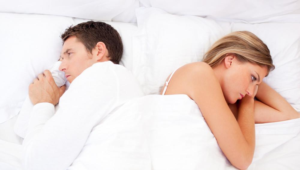 Paar liegt voneinander abgewandt im Bett.