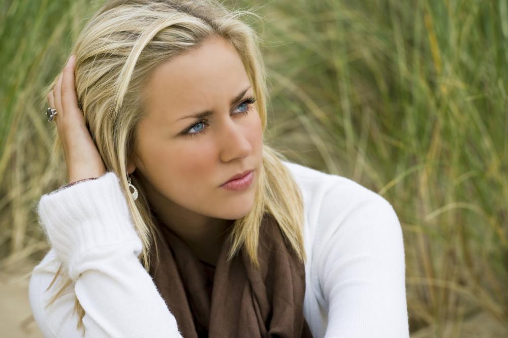 Einsame blonde Frau sitzt nachdenklich in den Dünen.