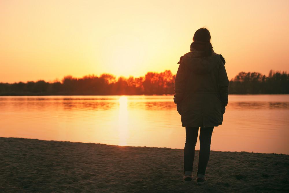 Eine junge einsame Frau steht alleine an einem See im Abendlicht.