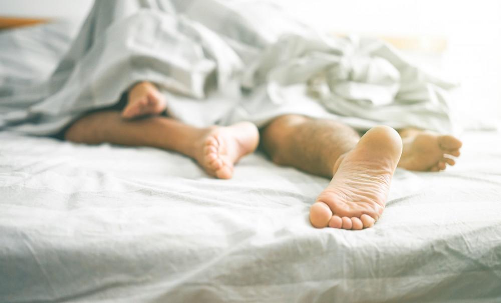 Füße schauen eines Paares unter einer Bettdecke hervor.