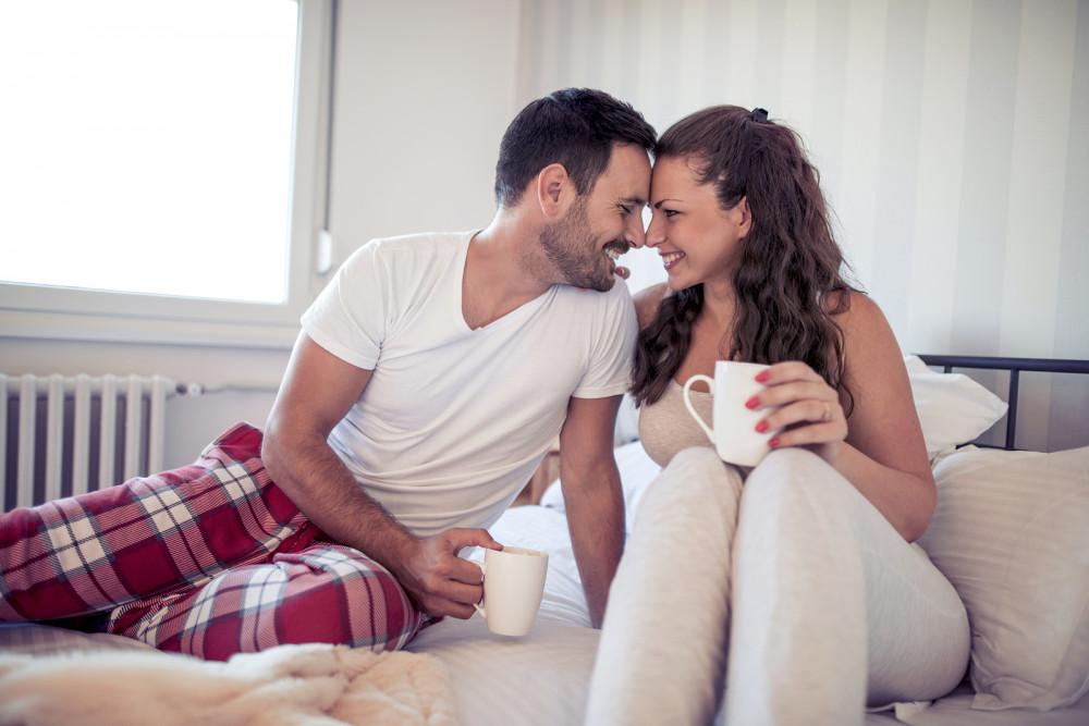 Glückliches Paar trinkt morgens Kaffee im Bett.