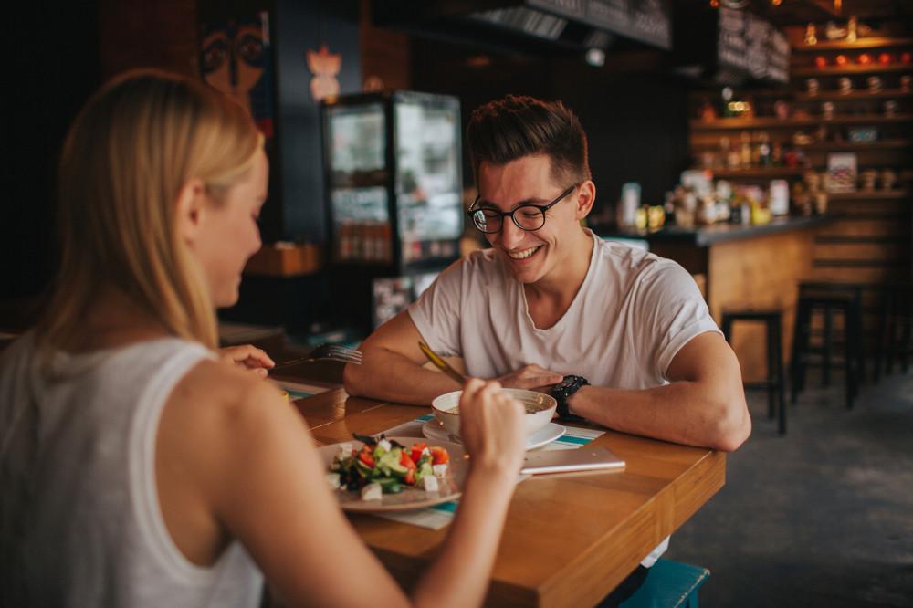 Zwei junge attraktive Singles sitzen bei einem Date im Café.