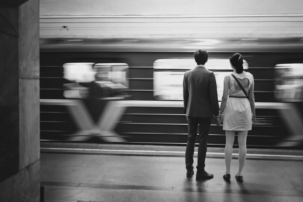 Paar steht gemeinsam in einem Bahnhof und schaut einem vorbeifahrenden Zug nach. Schwarz-Weiß.