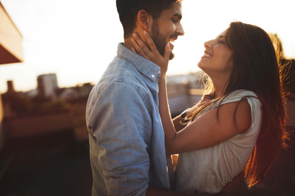 Verliebtes Paar schaut sich glücklich an und umarmt sich dabei.