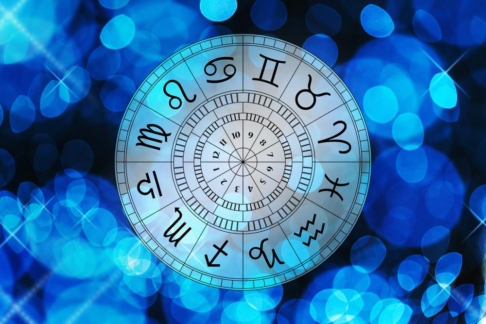 Sternzeichenaufteilung in Uhrenform vor blauem Hintergrund.