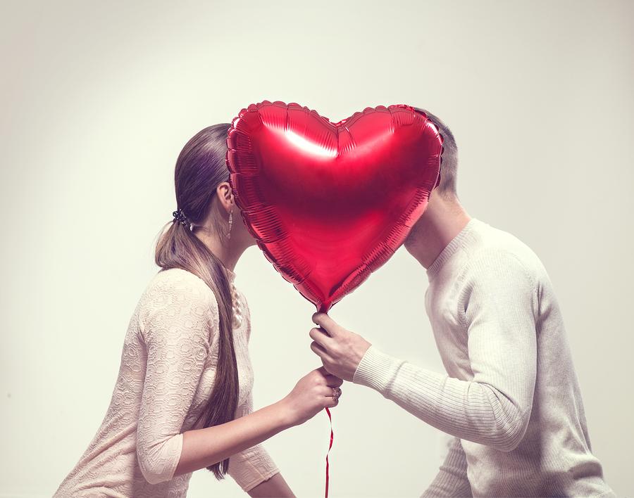 Paar küsst sich hinter Herz Luftballon.