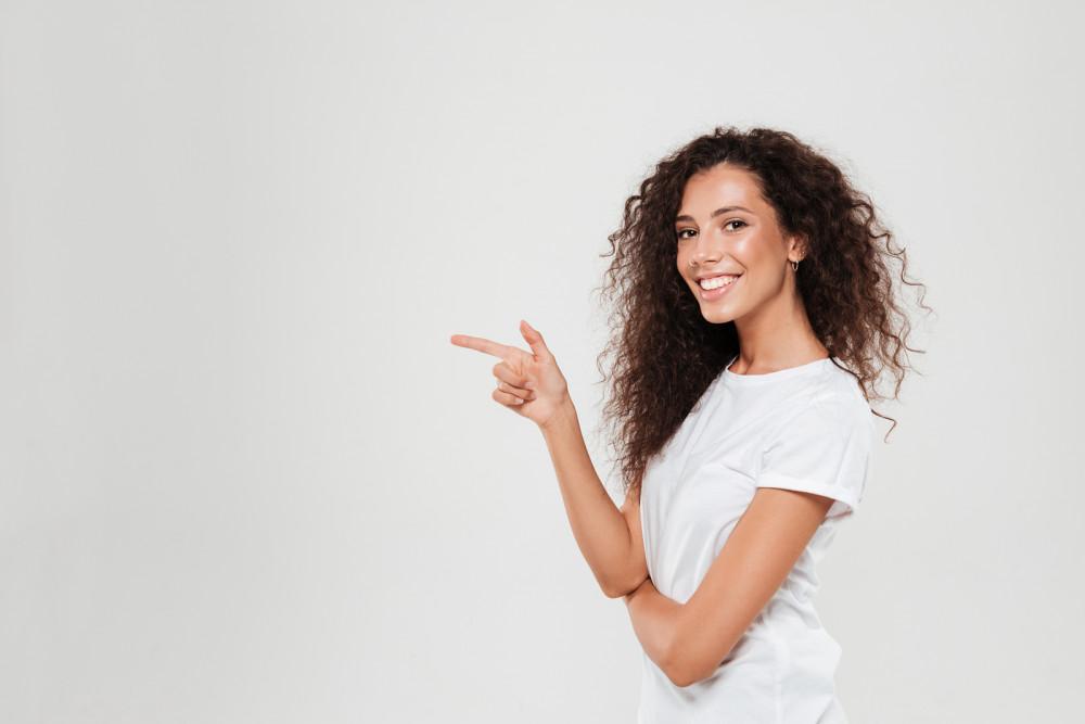Glückliche Single Frau mit lockigen Haaren vor grauem Hintergrund.