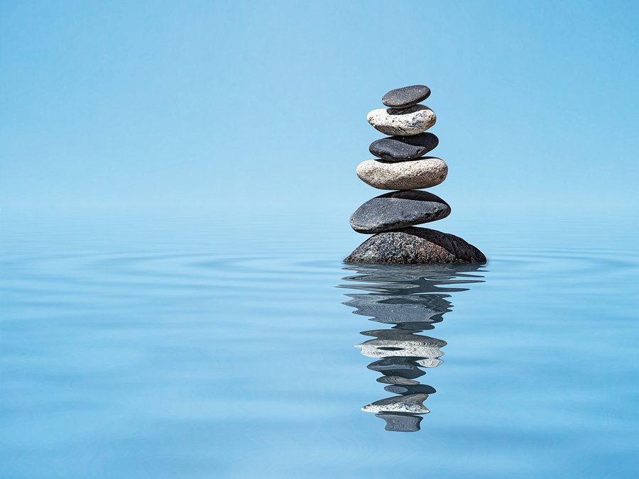 Steinturm, der sich im Wasser spiegelt.