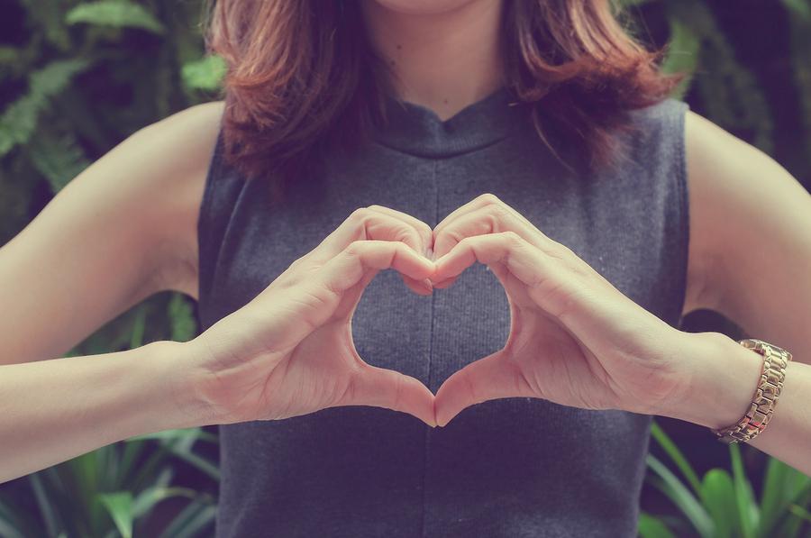 Verliebte Frau formt mit den Händen ein Herz.