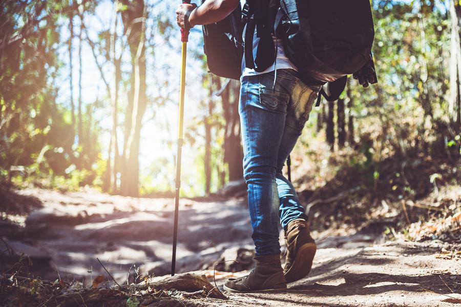 Mann mit Rucksack und Wanderstöcken unterwegs im Wald.